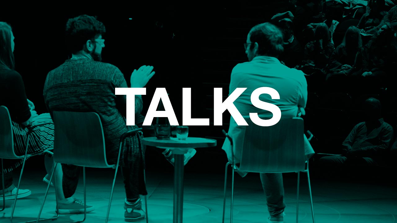 People sitting on stage talking to an audience, with the text Talks over the top