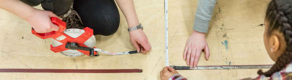 Young people learning how to measure out stage space as part of stage management course