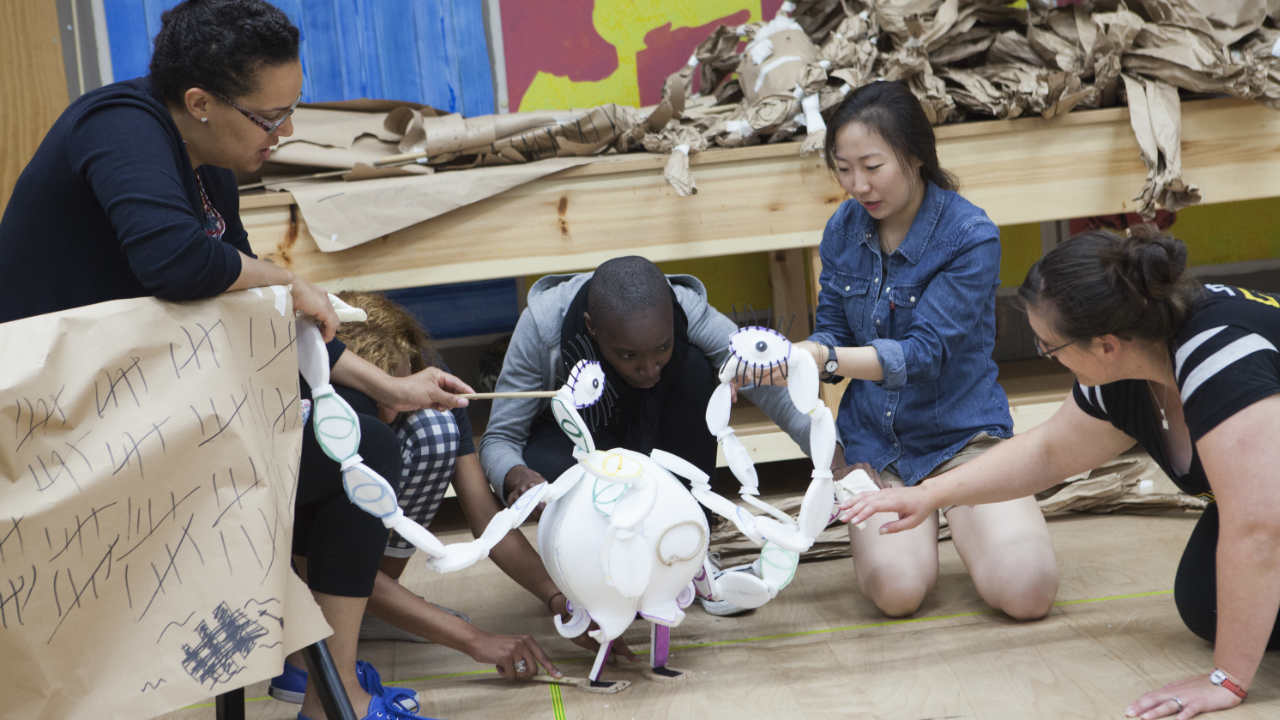 A photograph of young people manipulating a puppet