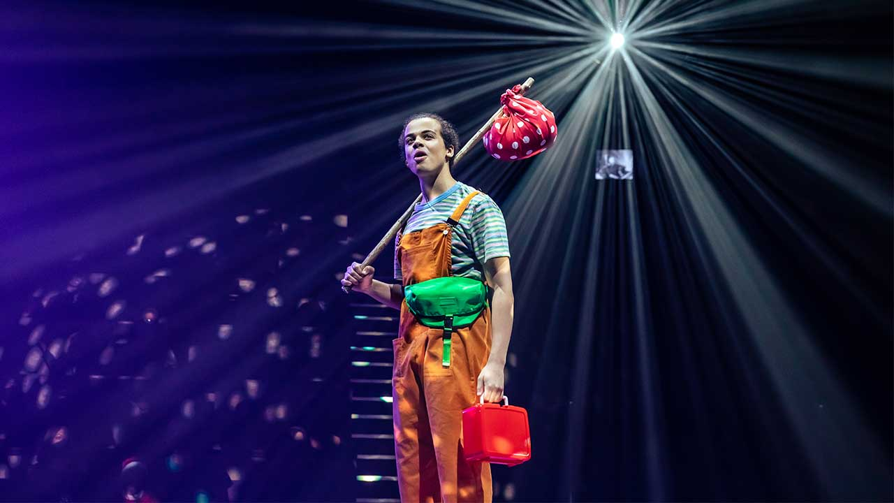 A young man in orange dungarees stands under a spotlight in Dick Whittington at the National Theatre.