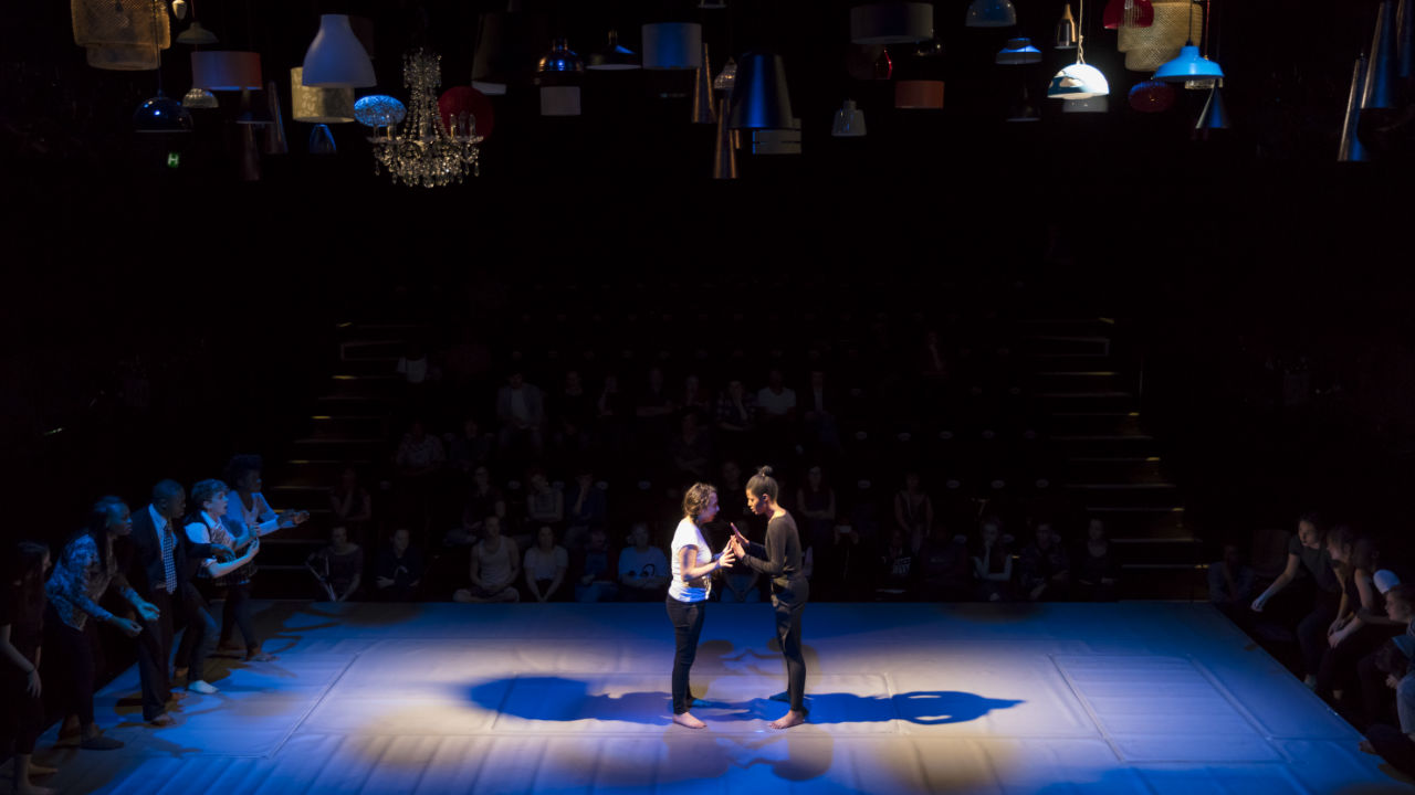 A wide shot of a stage lit in blue lighting, 2 young people standing face to face int he centre, other performers lining the sides