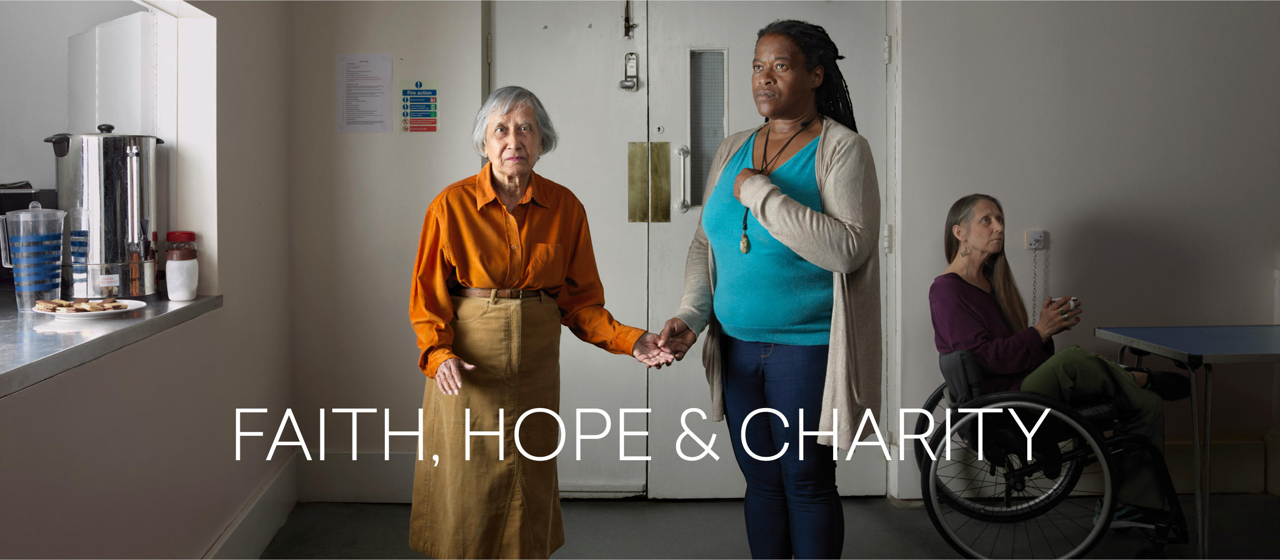 Faith, Hope and Charity poster: photo of three characters in a bare room with fire exit
