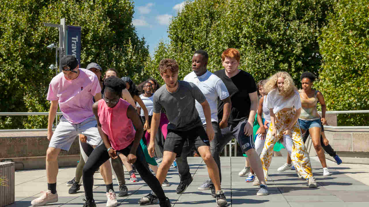 A photograph of a group of young people, dancing on the National Theatre terrace