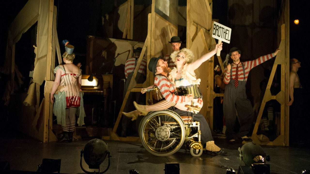 Jamie Beddard as Matthias in Threepenny Opera. Jamie sits in a wheelchair and a woman is straddling him. The woman is holding up a sign that says 'BROTHEL.'