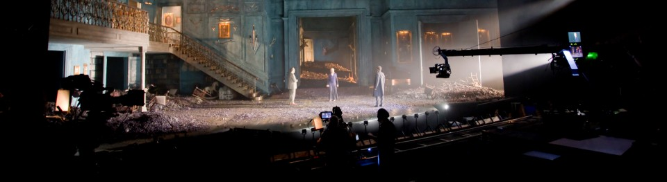 National Theatre Live performance of Hamlet being filmed, with a view of the stalls and the stage beyond, with cameras and audience in the foreground