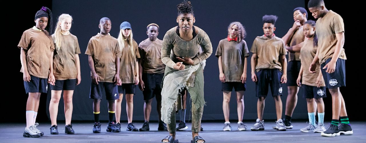 Production image of a Connections production of Terra Earth, with the acting company in a line across rear stage and a single member in front, squatting down.