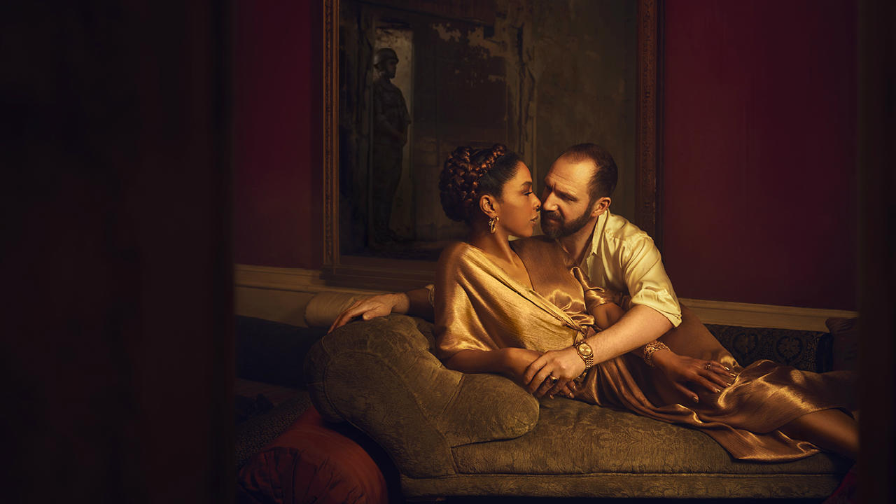 A photograph of characters Antony and Cleopatra, both wearing gold, laying on a day bed, almost kissing