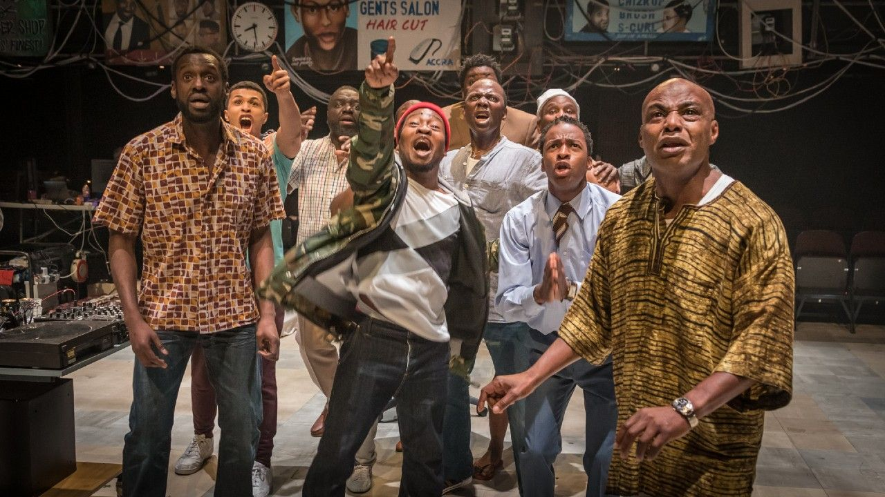 The Barber Shop Chronicles original NT cast production photo - a group of black men of varied ages, all facing towards the camera, looking up, excitedly.