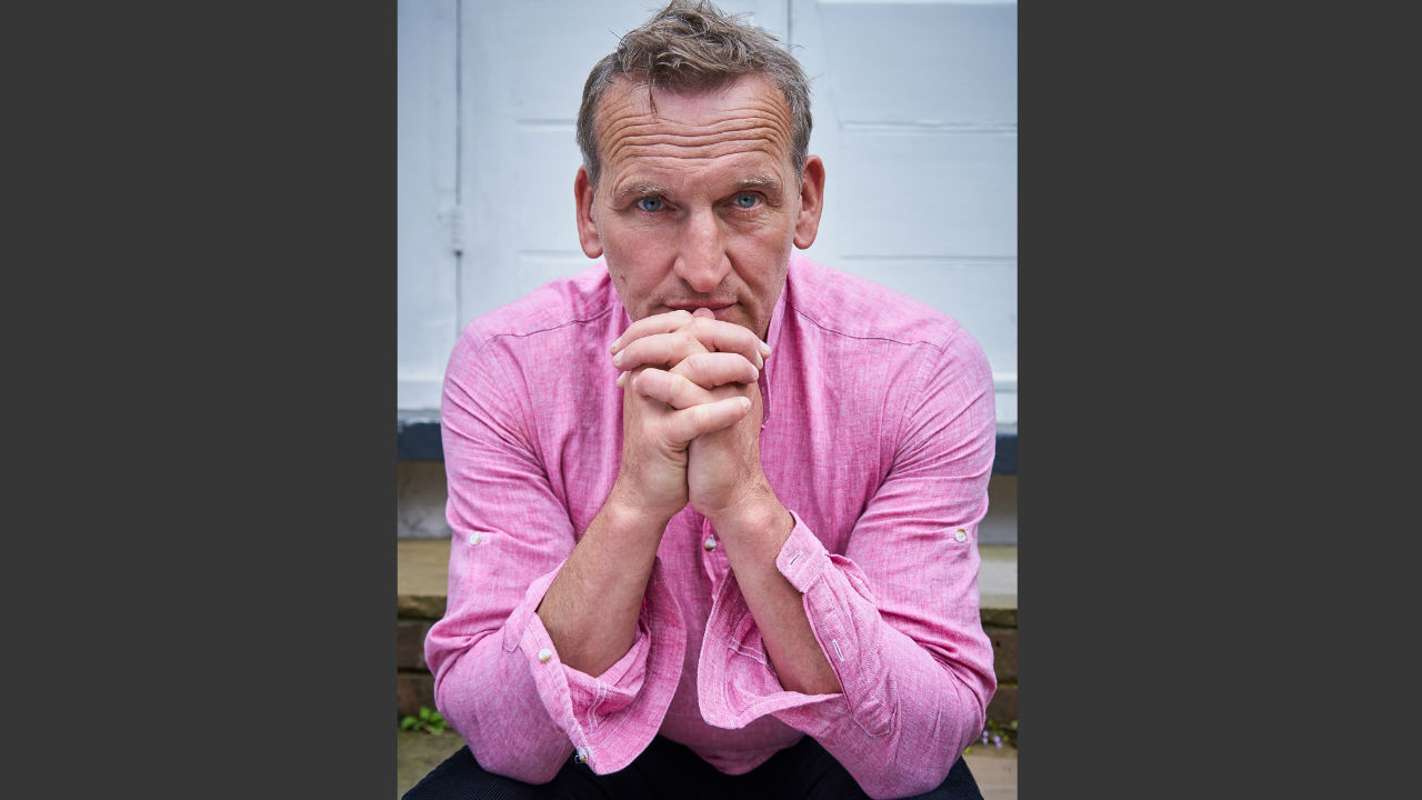 A photo of Christopher Eccelston wearing a pink shirt, taken for the front cover of his new book.