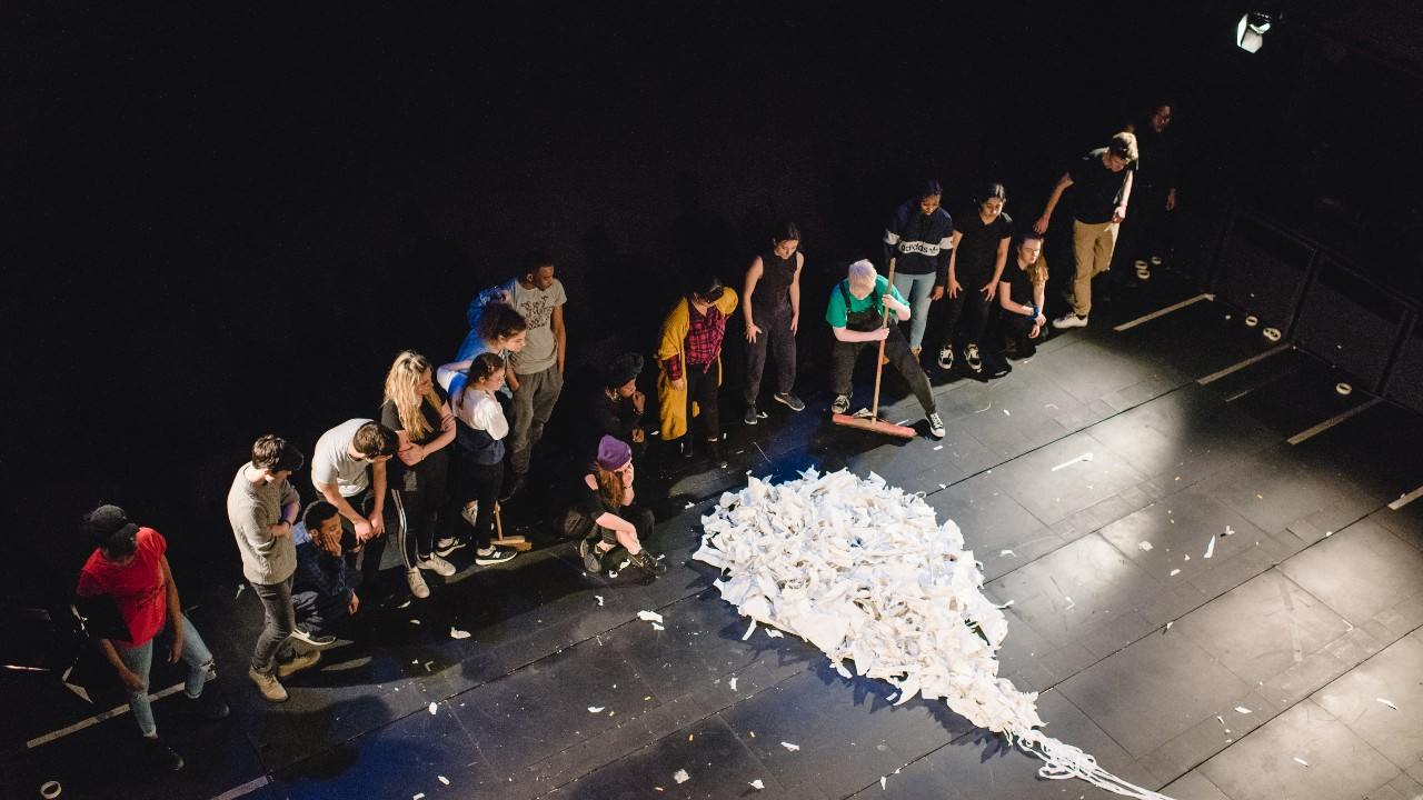 Young people on stage looking at set made from paper
