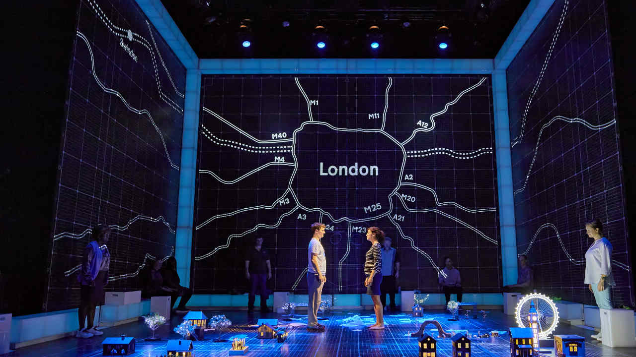 A wide photograph of the production on stage, a map of London in the background with actors int he space which is filled with miniature London landmarks