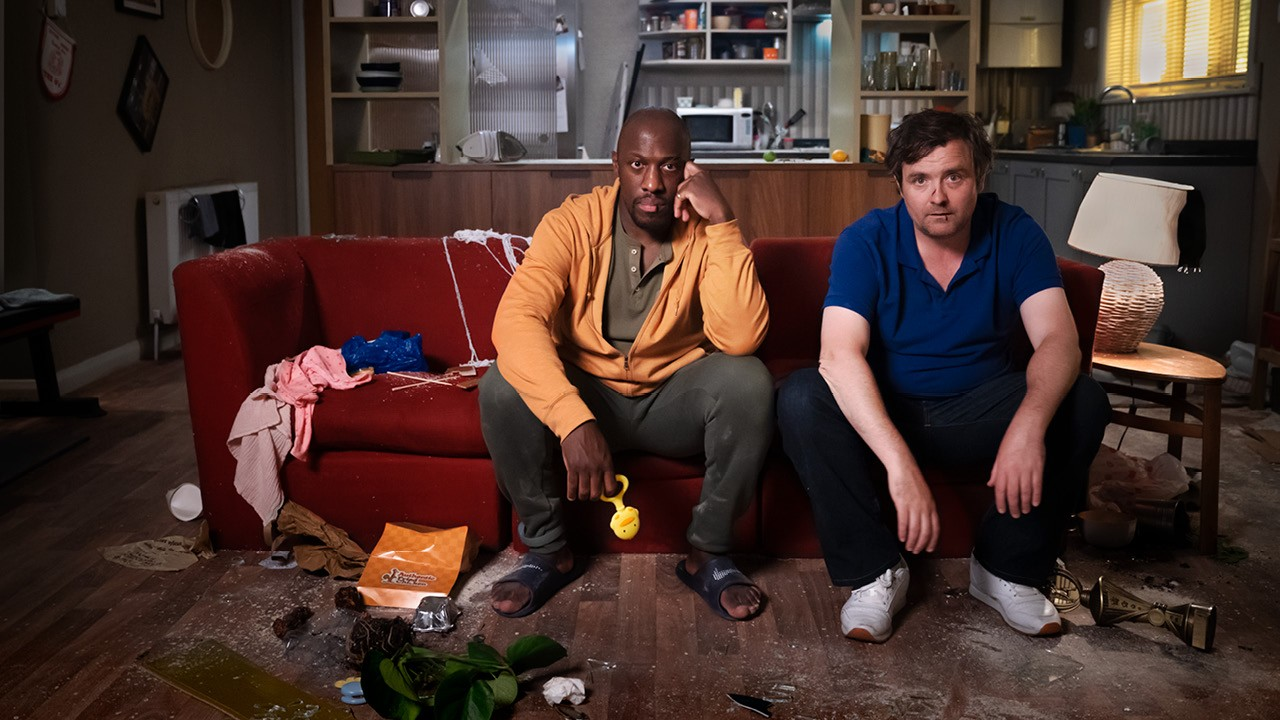 Death of England: Face to Face. Giles Terera and Neil Maskell as Delroy and Michael, sat on a sofa in Michael's messy flat.
