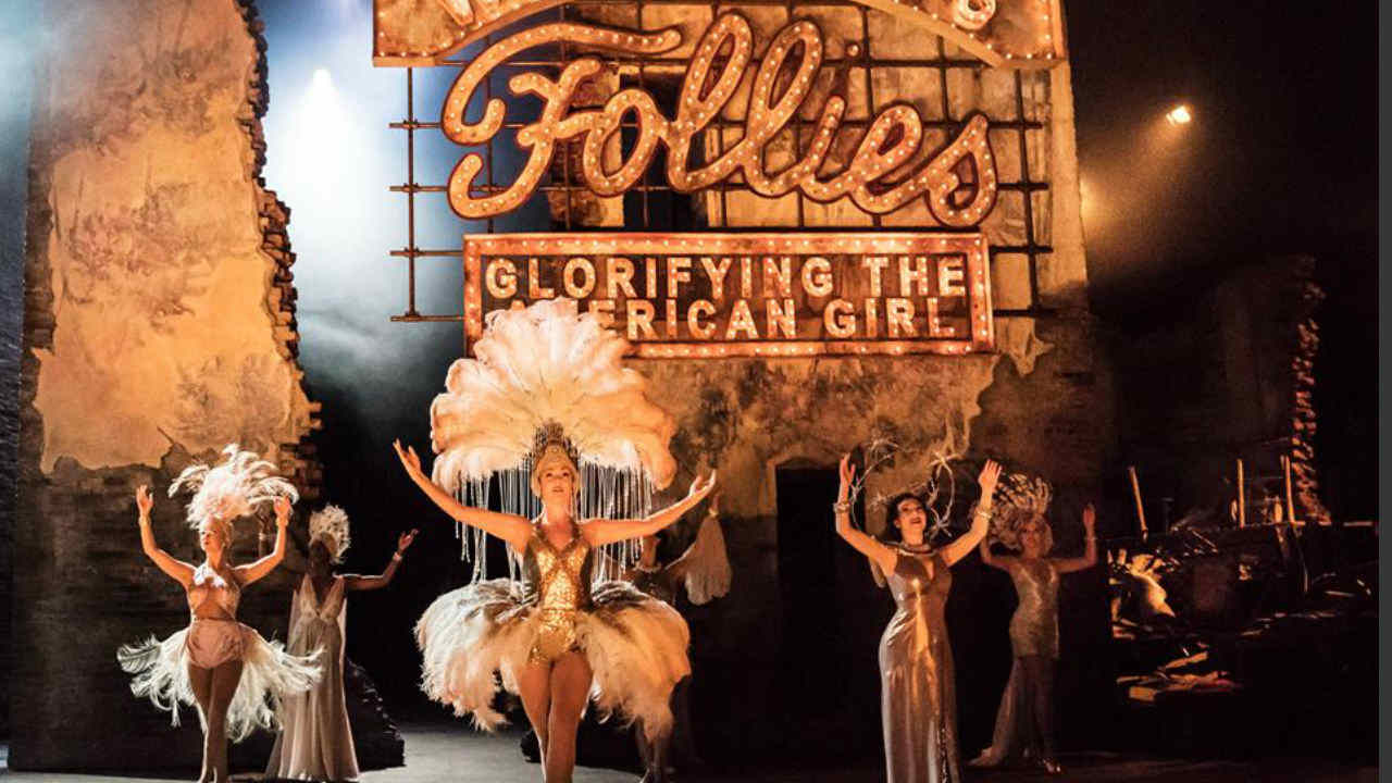 A production photograph of Follies dancers on stage in their costumes.