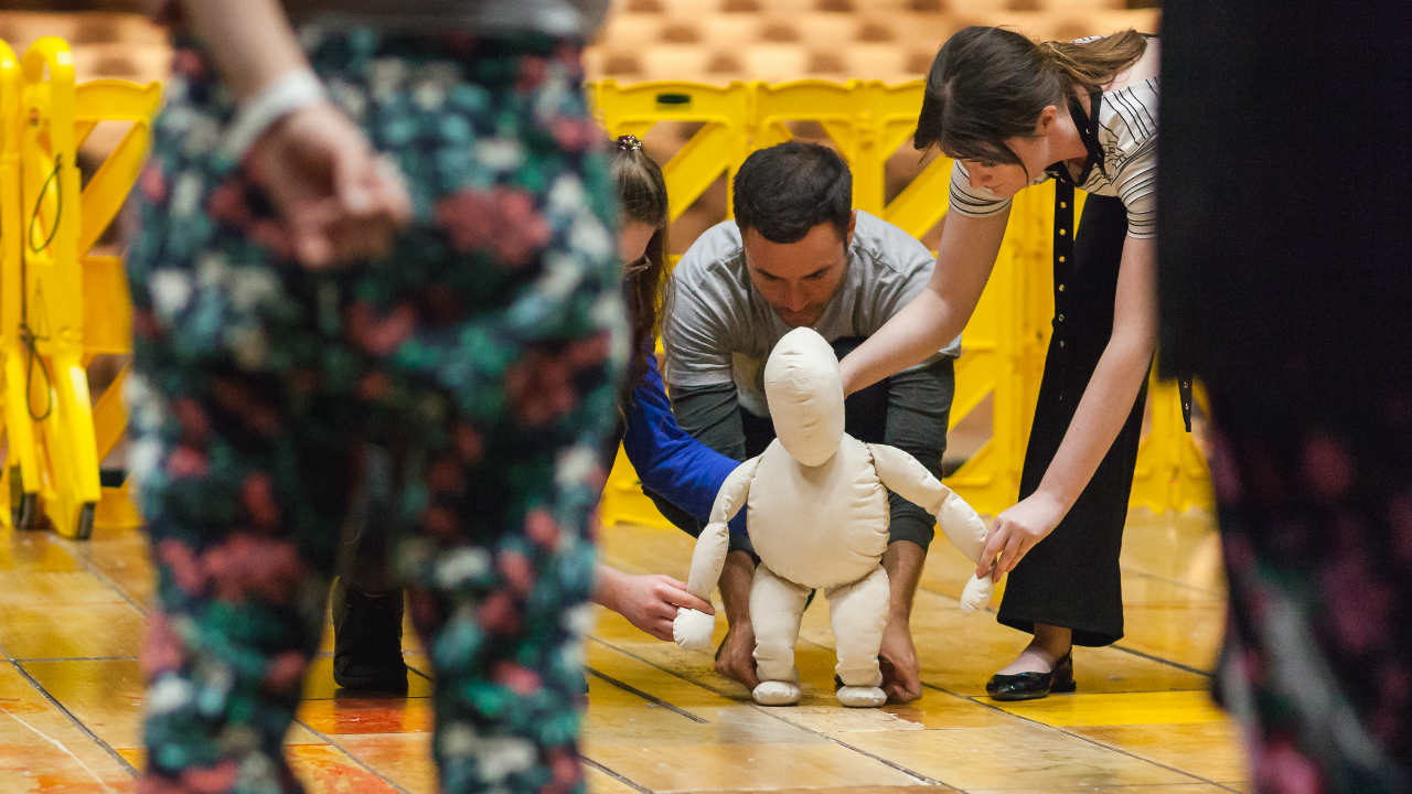 A group of adults manipulating a puppet