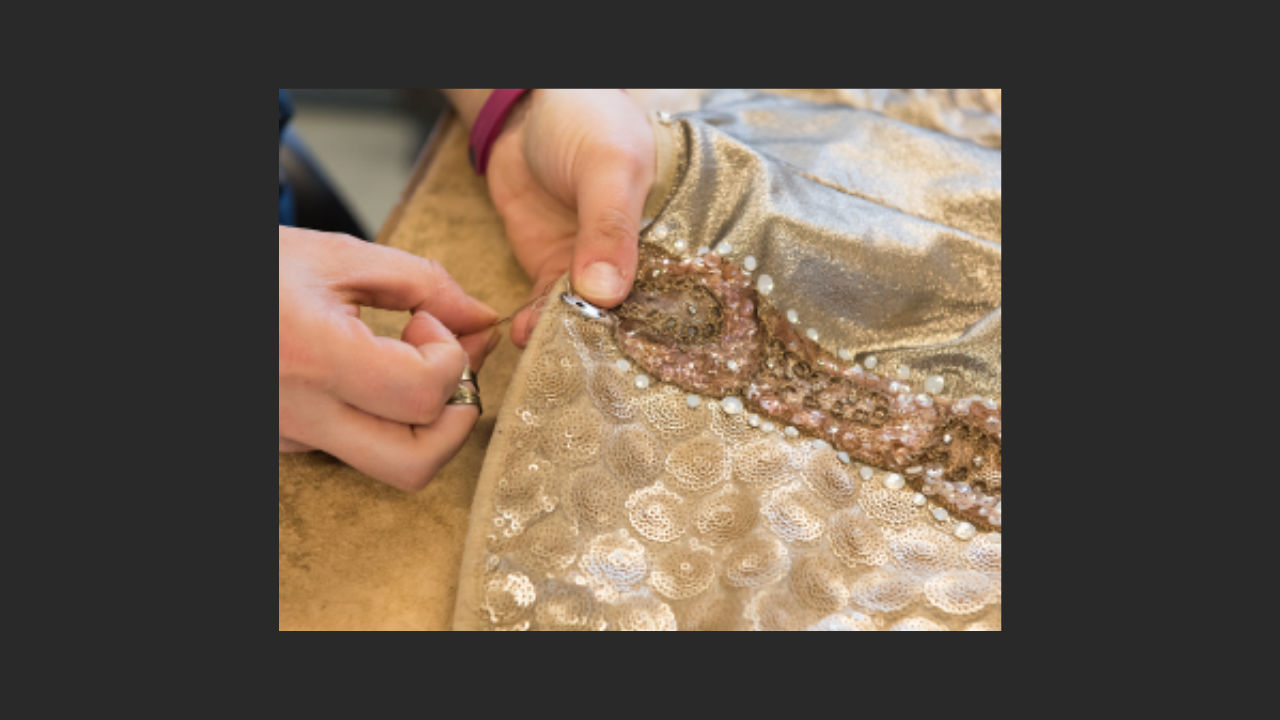 a photo of intricate hand sewing on a gold costume