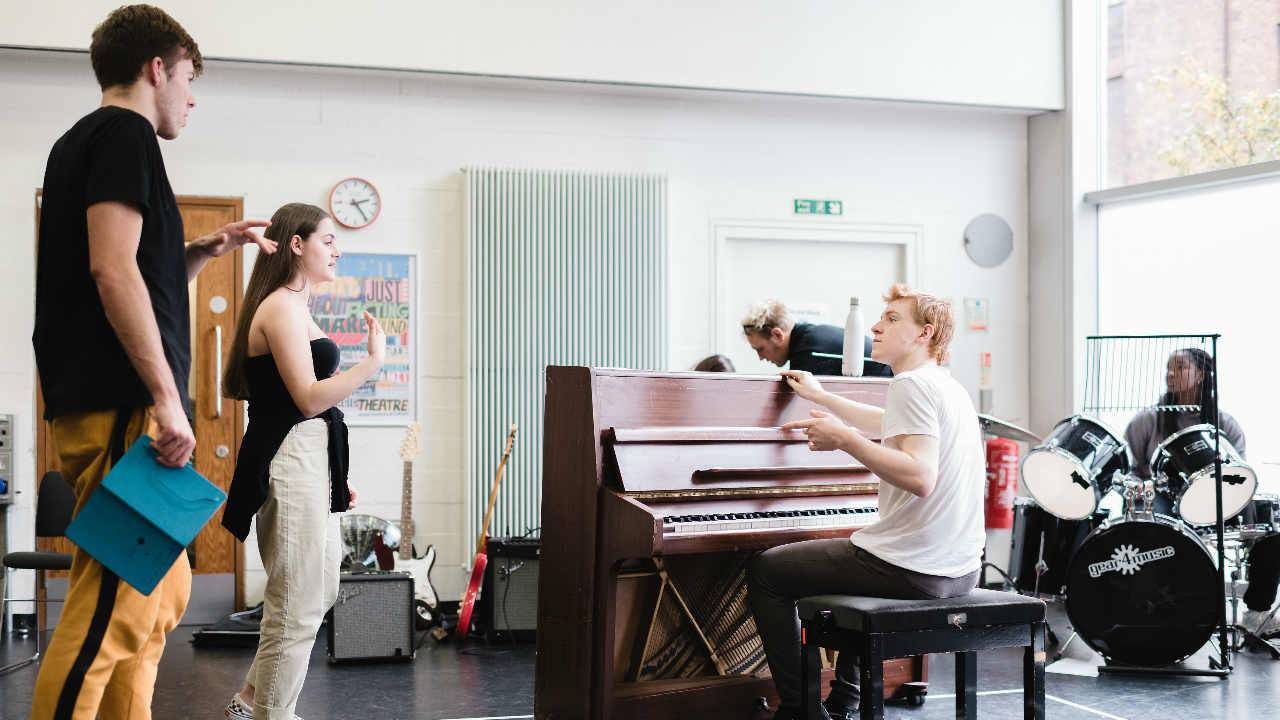 Young people in a music workshop with piano and percussion instruments