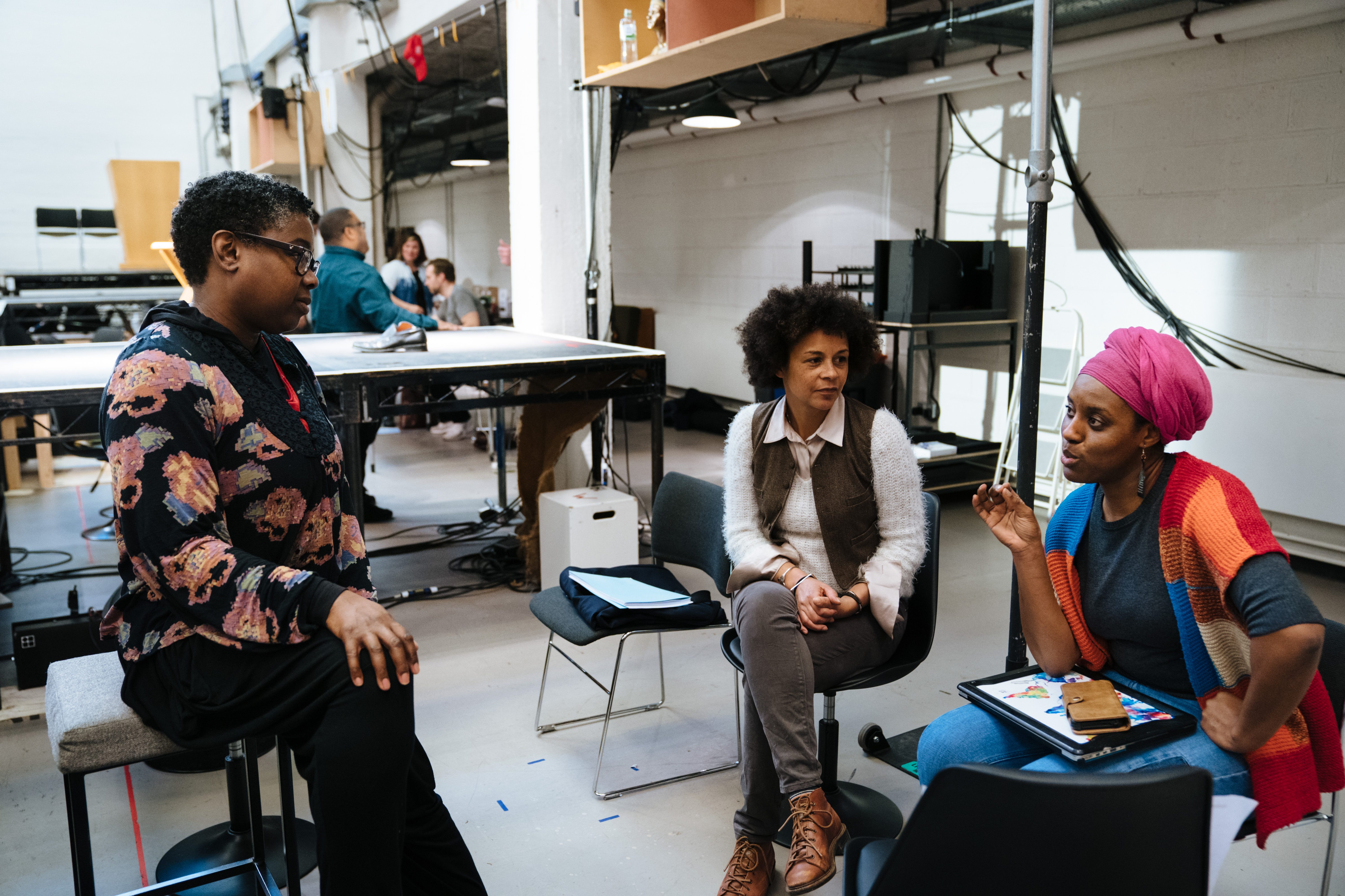 Hazel Holder, Sian Ejiwunmi-Le Berre, and Sadeysa Greenaway-Bailey work together at the National Theatre's New Work Department