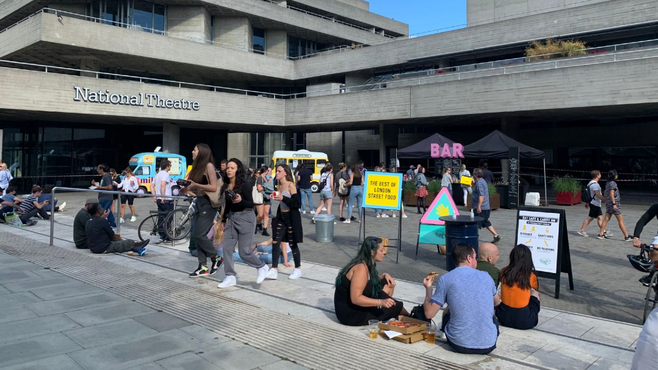 Kerb streetfood stalls outside the National Theatre with people eating on the steps