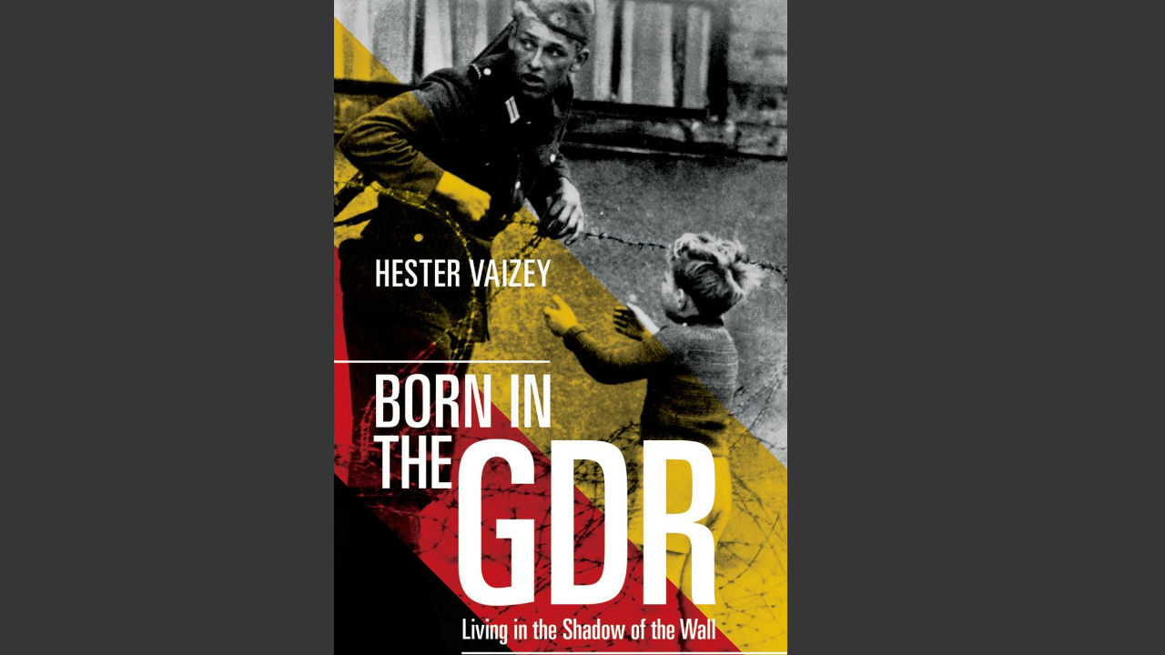 The front cover of the book 'Born in the GDR: Living int he Shadow of the Wall' - a photograph of an military officer and a young boy leaning over barbed wire