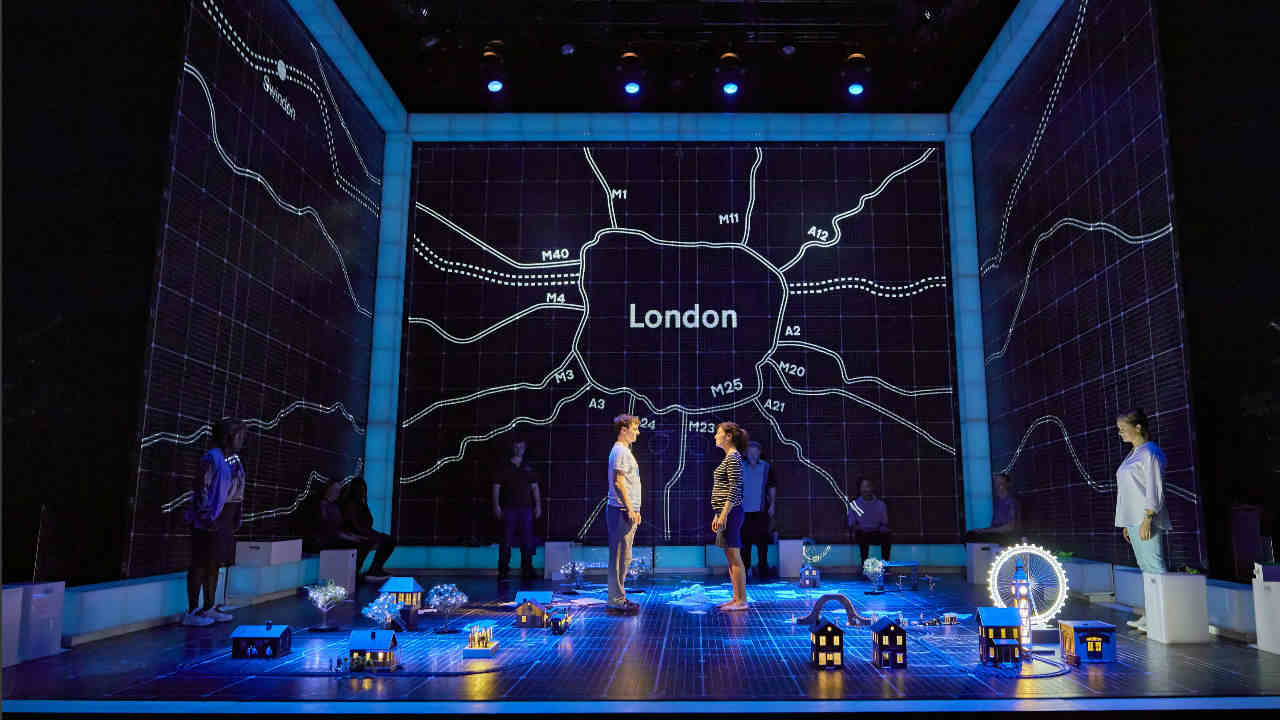 A photograph from a Curious Incident performance: the background in a map of London, Christopher and his mum stand in front, looking at each other