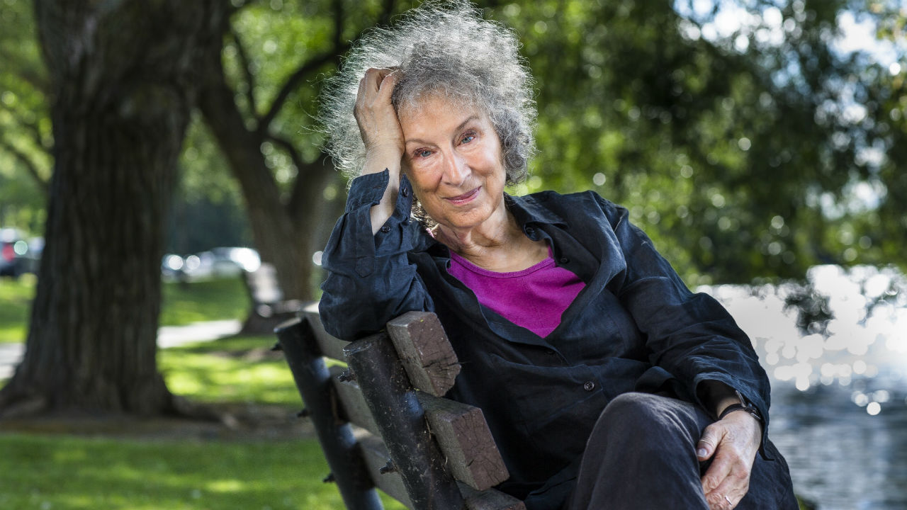 Margaret Atwood photographed sitting on a park bench