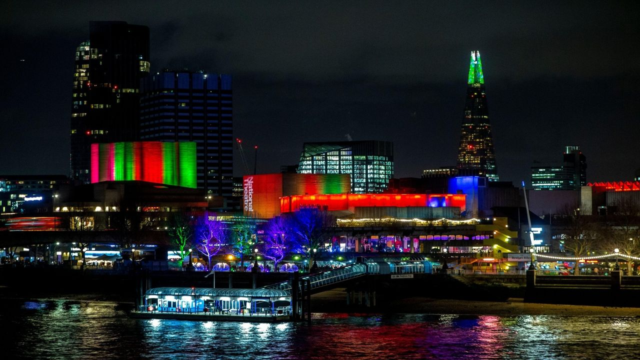 National Theatre at Night, illuminated with different coloured light, with teh Thames in front.