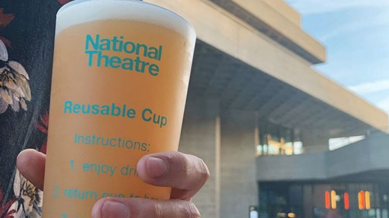 National Theatre re-usable cup, filled with beer being held