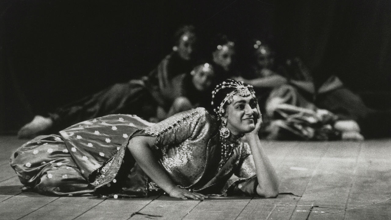 Meera Syal as Anitra in Peer Gynt (1990) - a female laid on the stage, head in hand, smiling