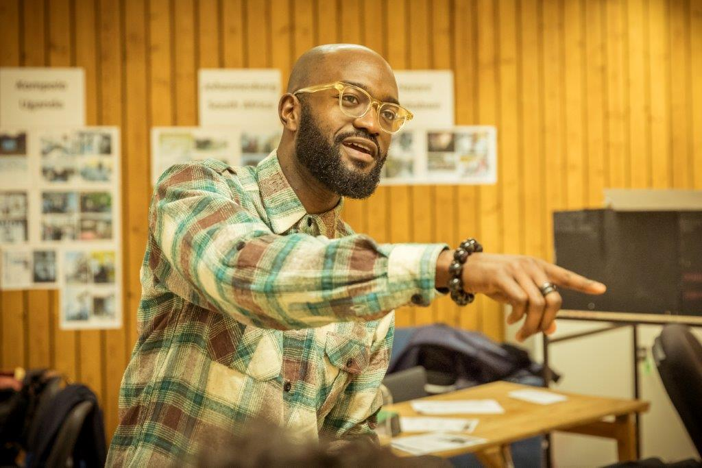 This is a photo of playwright Inua Ellams in rehearsal for Barber Shop Chronicles