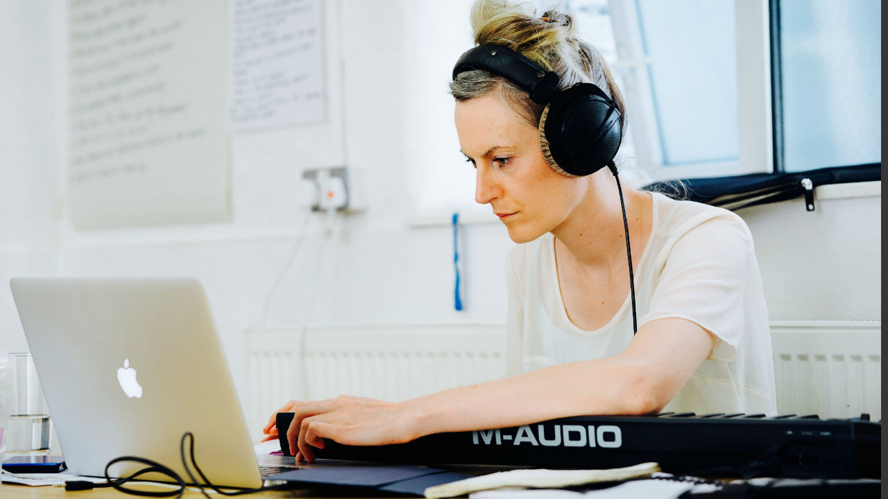 A photograph of Melanie Wilson working, non a laptop and keyboard