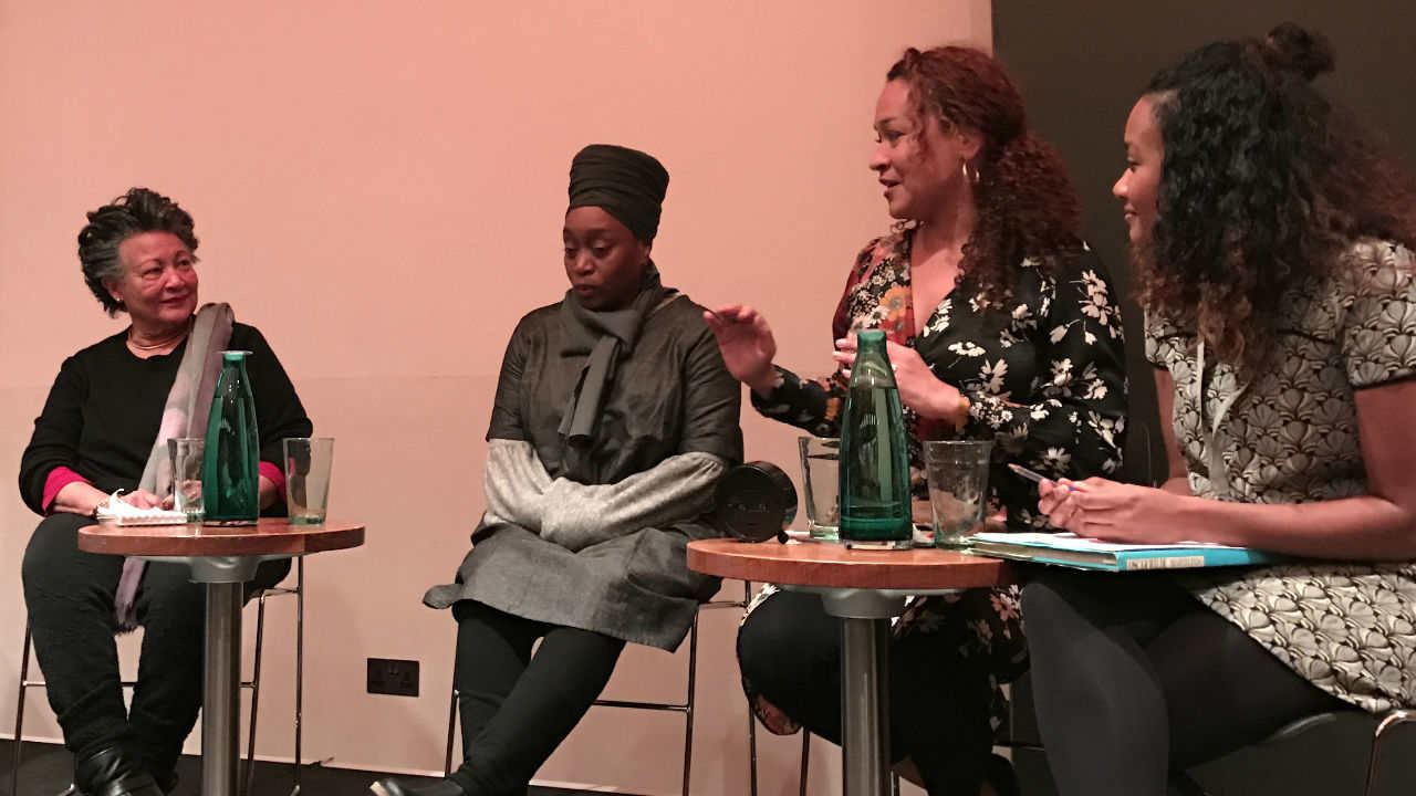 A photograph of a panel discussion showing four black women sat on stage