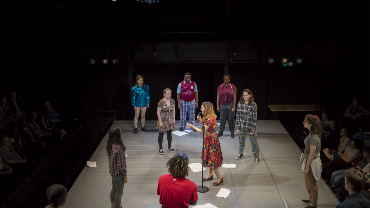 A photograph of young people standing on stage, in performance
