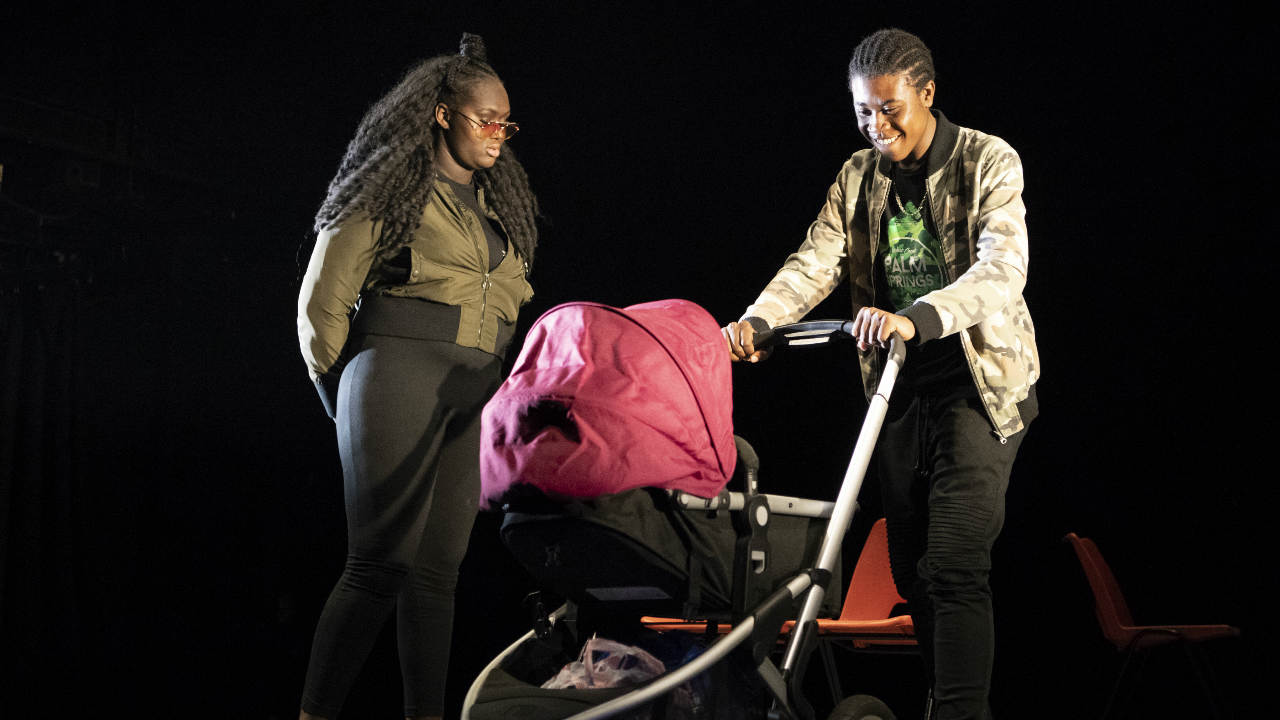 A black background, a young man and young woman are on stage with a pram