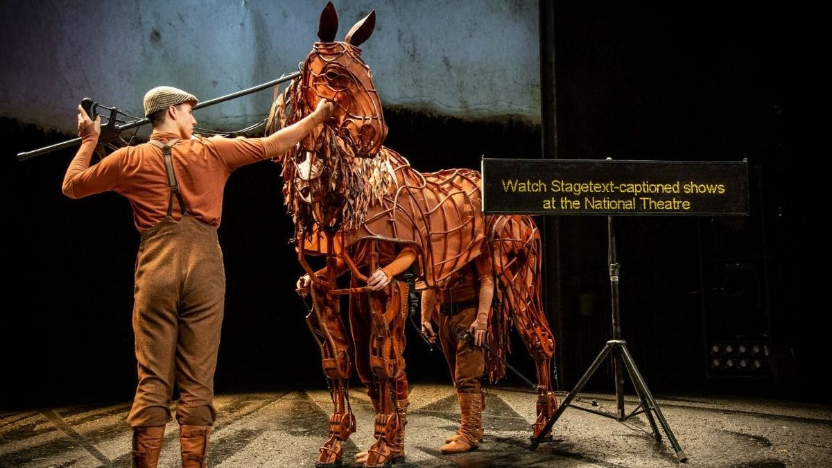 War Horse Captioned performance image, with Joey and handlers and a captioned unit on stage