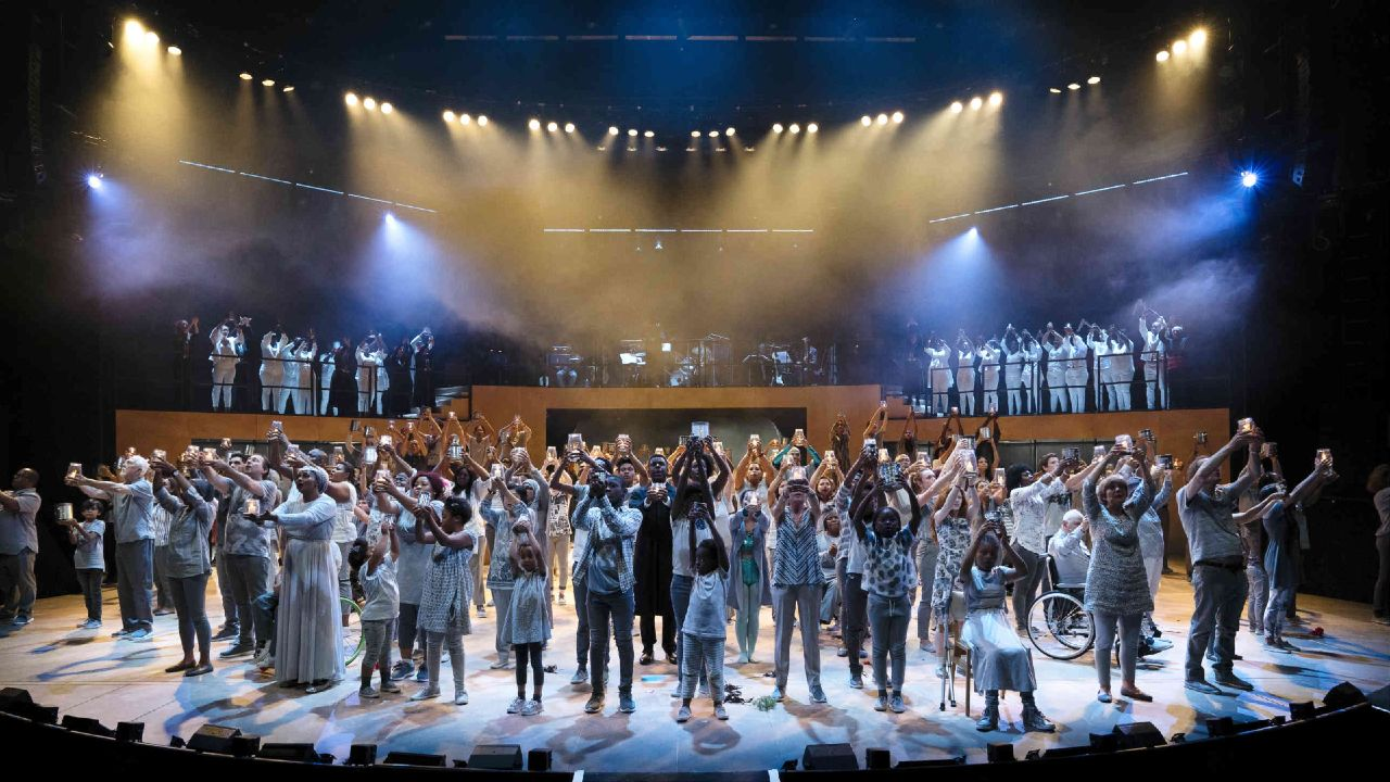 The ensemble lift their hands towards the audiences, from Pericles, a Public Acts performance, on the Olivier Theatre stage at the National Theatre