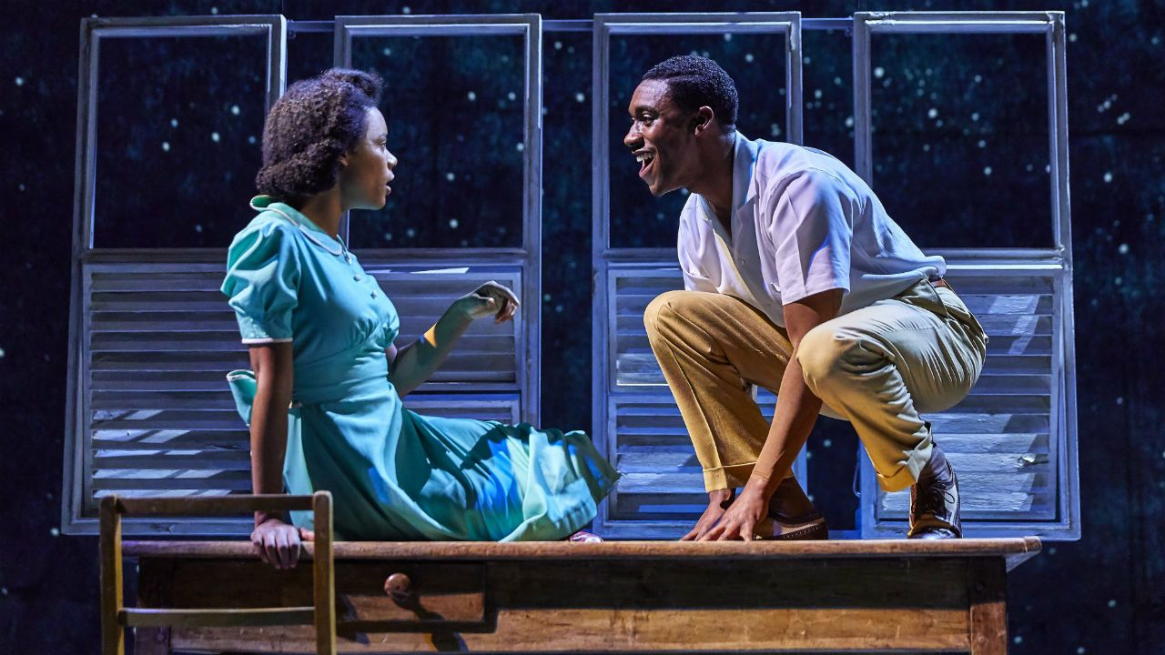 Small Island production photo Leah Harvey and company member on a table with windows and stars behind