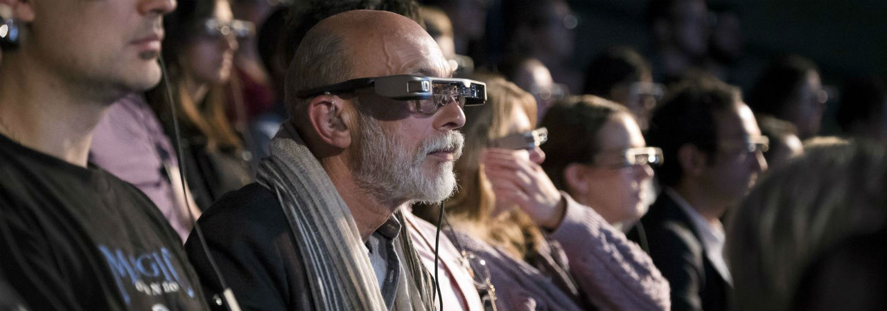 A row of audience members wearing smart caption glasses.