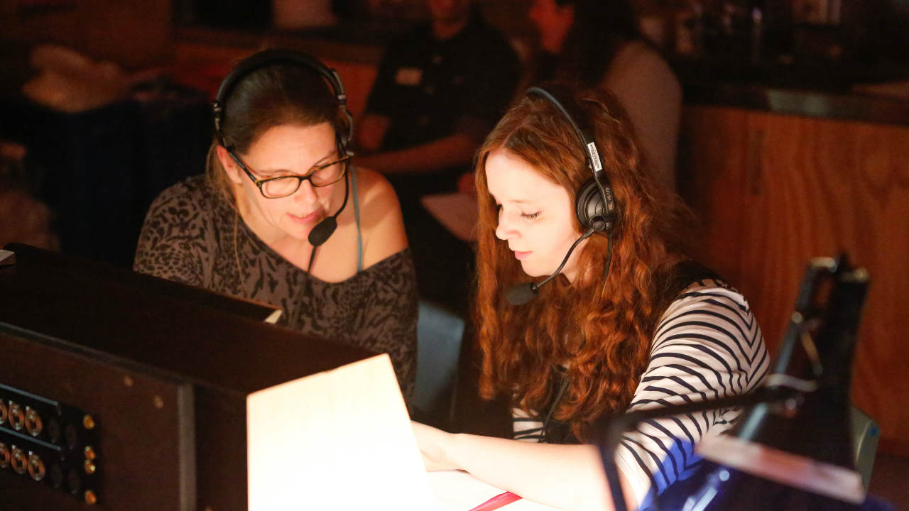 A photograph of two young women wearing headsets, sitting at a desk