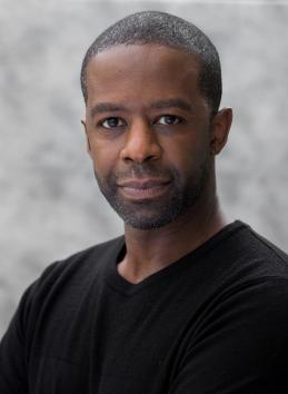 Photo portrait of Adrian Lester in a black crew-neck top