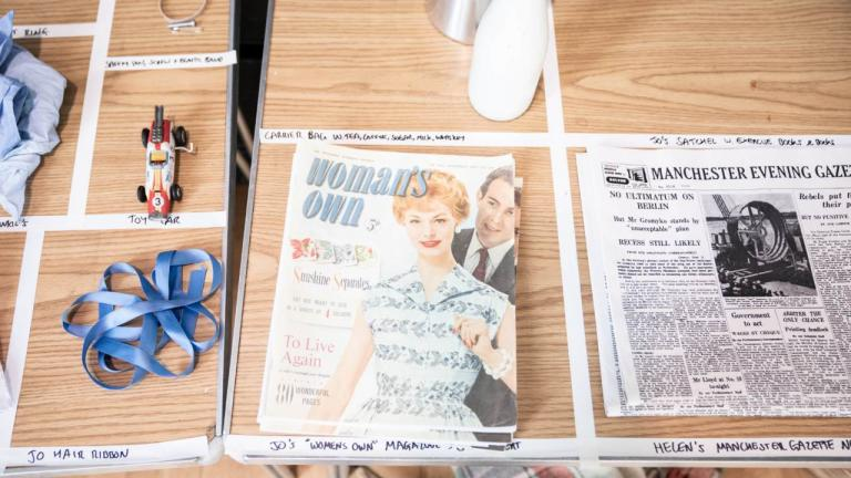 A Taste of Honey tour rehearsal image - Props laid out on a table, including Woman's Own magazine and a Manchester Evening Gazette