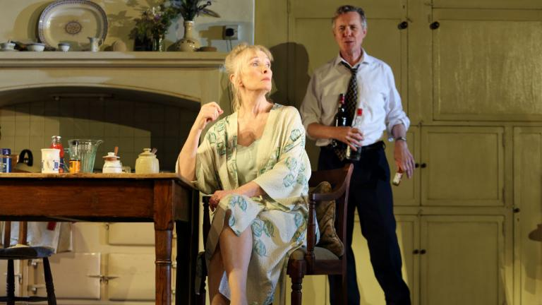 Image of Diana (Lindsay Duncan) sat at the kitchen table. Robin (Alex Jennings) is stood behind with drinks in hand.