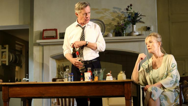 Image of Diana (Lindsay Duncan) sat at the kitchen table. Robin (Alex Jennings) is stood next to her with drinks in his hand.