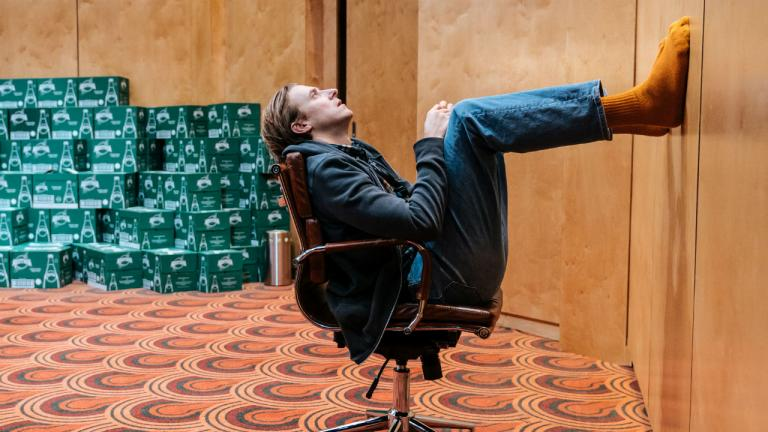 Arthur Darvill sits on a chair with his feet up on the wall. He is wearing yellow socks.