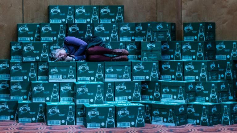 Sinead Matthews lies down with her eyes closed on boxes of Perrier water.