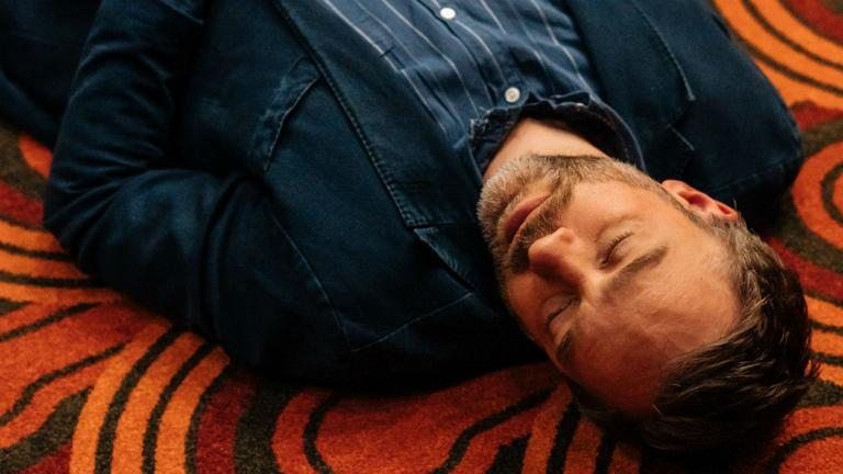 A close up of Hadley Fraser lying down on the carpet. His eyes are closed.