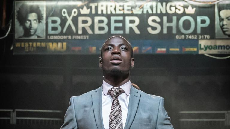 Barber Shop Chronicles at the Roundhouse: a man in a suit, standing beneath a poster for the Three Kings Barber Shop
