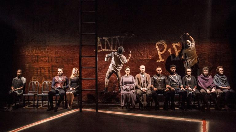 Coriolanus production image of the company, mostly seated in a row, facing forward