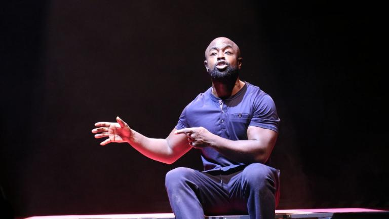 Death of England: Delroy Production photo of Michael Balogun, in blue t-shirt and trousers, sitting, hands gesturing to his right, speaking