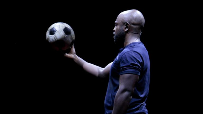 Death of England: Delroy Production photo of Michael Balogun, in blue t-shirt, holding a football in his outstretched hand