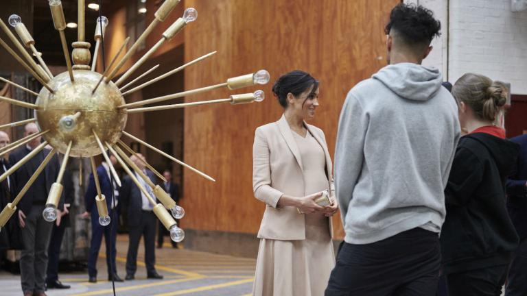 Duchess of Sussex with Technical Apprentices Kelsey Smith and Olivia Richardson. She is standing next to a gold chandelier. It is very modern, with bulbs on sticks sticking out of a central gold ball.